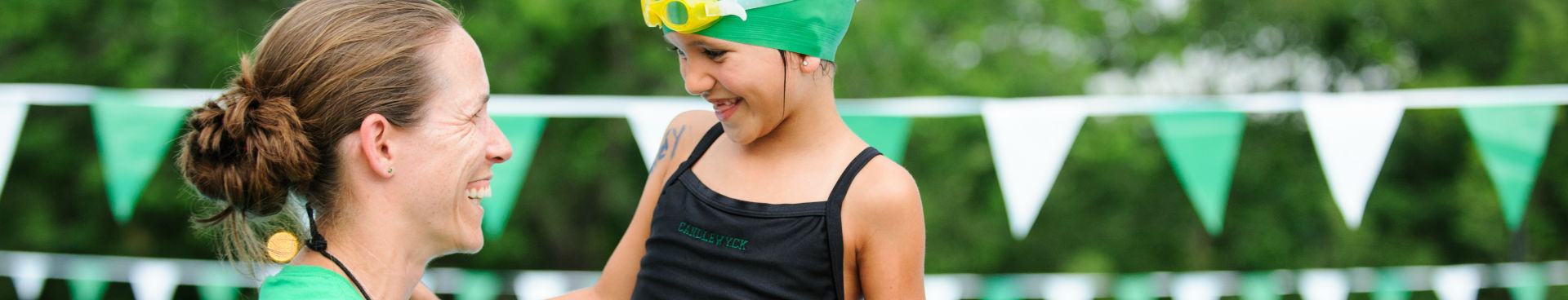 Young girl and coach at swim meet smiling
